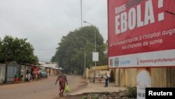 FILE - A billboard with an Ebola message looms over a street in Conakry, Guinea, Oct. 26, 2014.