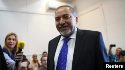 Former Israeli Foreign Minister Avigdor Lieberman (C) smiles as he waits to hear the verdict in the corruption charges against him at the Magistrate Court in Jerusalem, Nov. 6, 2013.