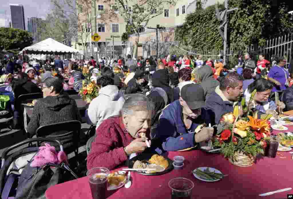 Para tuna wisma dan orang-orang yang kurang mampu di wilayah Skid Row, Los Angeles, mendapatkan makanan gratis dalam perayaan tahunan Thanksgiving (25/11). (AP/Nick Ut)
