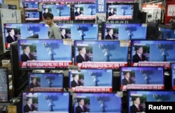 FILE - A sales assistant in Seoul, South Korea, watches TV sets broadcasting a news report on North Korea's nuclear test, Jan. 6, 2016.