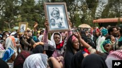 FILE - Relatives mourn as they lift portraits of family members they lost in the collapse of a mountain of trash at a garbage dump, during a funeral service held at Gebrekristos church in Addis Ababa, Ethiopia, March 13, 2017.