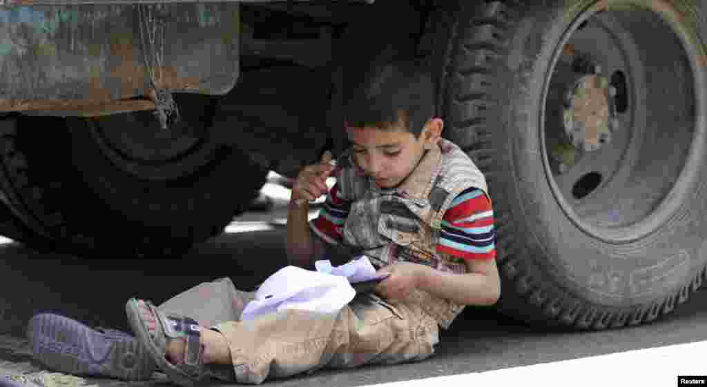 A boy sits near a wheel of a transport vehicle to memorize his lessons on Siteen Road in Sana'a, Yemen.