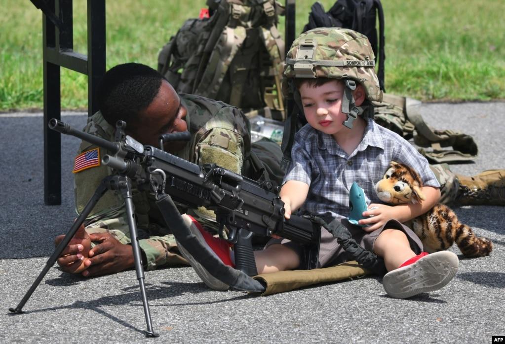 Американский солдат смотрит на мальчика, позирующего с легким пулеметом M249 во время церемонии в честь 75-й годовщины Восьмой армии США в лагере Хамфрис в Пхентхэке, Южная Корея, 8 июня 2019 года.