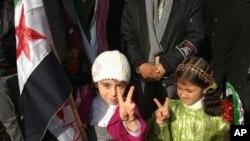 Qîzên Kurd li bajarê Amude, bi tilîyên xwe nîşana serkeftinê fikin, li dijî serok Beşar Esed.