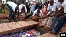 Des volontaires déposent dans caveau les restes des victimes du génocide de 1994, à Murambi, est du Rwanda, 07 avril 2005. epa / RICKY GARE
