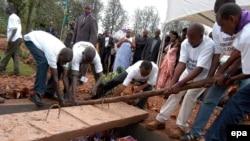Des volontaires déposent dans un caveau les restes de victimes du génocide de 1994, à Murambi, est du Rwanda, 07 avril 2005. epa / RICKY GARE