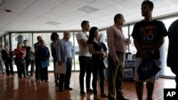 FILE - People stand in line to register for a job fair in Miami Lakes, Florida, July 19, 2016.