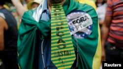 Com uma gravata e a bandeira nas costas, manifestante protesta a corrupção do governo