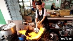 Chef Fai Junsuta cooks at her street restaurant Jay Fai in Bangkok, Thailand. (YouTube)