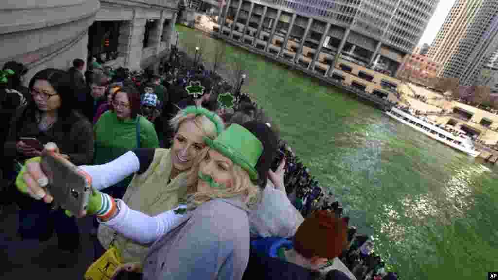 Alex Nowakowska, kiri, dan Joanna Puchlik, kanan, keduanya dari Chicago, mengambil foto selfie di Sungai Chicago yang diwarnai hijau sebelum parade Hari St. Patrick di Chicago, 14 Maret 2015.