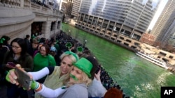 Chicago residents take a selfie after the Chicago River is dyed green ahead of the St. Patrick's Day parade.