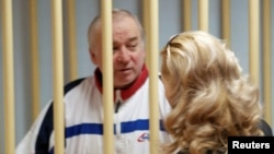 FILE - Sergei Skripal, a former colonel of Russia's GRU military intelligence service, looks on from the defendants' cage at a hearing at the Moscow military district court, Russia, Aug. 9, 2006.