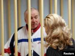 FILE - Sergei Skripal, a former colonel of Russia's GRU military intelligence service, talks to an unidentified woman from inside a defendant's cage as he attends a hearing at the Moscow military district court, Russia, Aug. 9, 2006. Skripal ended up in Briatin as part of a spy swap.