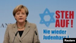 """La canciller Angela Merkel habla frente a un letrero que dice """"Levántese!"""" durante un evento para combatir el antisemitismo en Berlin."""