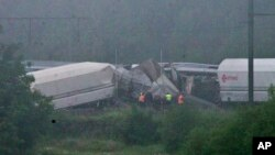 Nhân viên cứu hộ đứng gần hiện trường vụ tai nạn xe lửa ở Hermalle-sous-Huy, gần Liege, Bỉ, ngày 6 tháng 6 năm 2016.