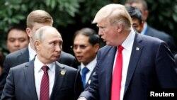 U.S. President Donald Trump and Russia's President Vladimir Putin talk during the photo session at the APEC Summit in Danang, Vietnam, Nov. 11, 2017.