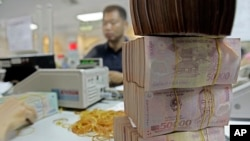 FILE - Vietnamese money Dong is seen in Asia Commercial Bank in Hanoi, Vietnam. (AP Photo/Chitose Suzuki)