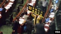 梁振英(持公事包者)步出立法會會議廳時,人民力量議員陳偉業向他高舉示威標語,要求他下台。 (美國之音 湯惠芸攝)