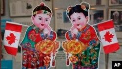 2010年2月18日,加拿大的不列顛哥倫比亞省的溫哥華,在中國城一座商業大樓的入口處,有加拿大國旗和華人慶祝農曆新年的招財進寶童男童女畫像。