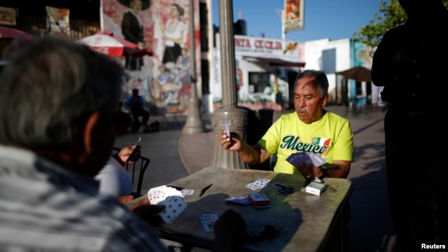 FILE - Men play cards in Mariachi Plaza in the Boyle Heights area of Los Angeles, home to many Mexican and Central American migrants, Aug. 9, 2014. Seven men have been charged in firebombings that drove blacks from their homes in the neighborhood.