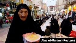 Muslim Irak berkumpul untuk berbuka puasa selama buka puasa bersama di jalan selama bulan suci Ramadhan di Najaf, Irak, 18 April 2021. (Foto: REUTERS/Alaa Al-Marjani)