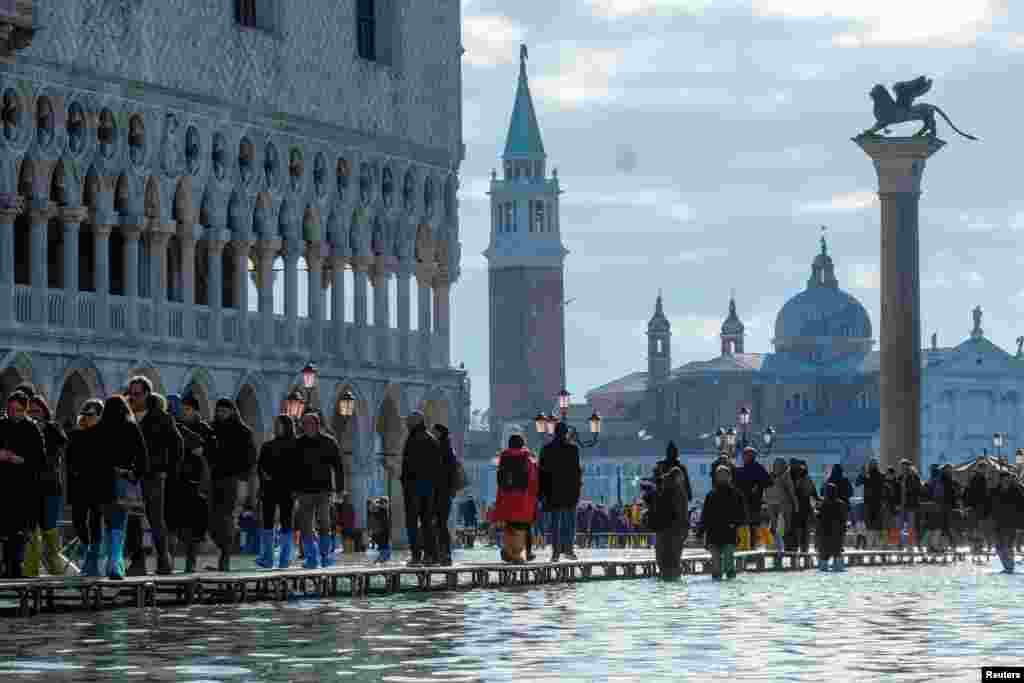 People use a makeshift walkway over the flooded St. Mark's Square in Venice, Italy.