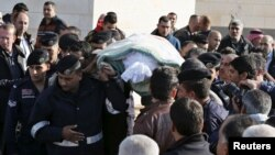Police officers and relatives of Kamal Milkawi, one of the Jordanians killed in a shooting incident at a U.S.-funded police training facility near Amman, carry his body during his funeral in Zarqa, Jordan, Nov. 10, 2015.