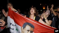 Supporters of Syrian President Bashar al-Assad shout slogans holding their country's flag with a superimposed Assad portrait, Damascus, Syria, August 20, 2011.