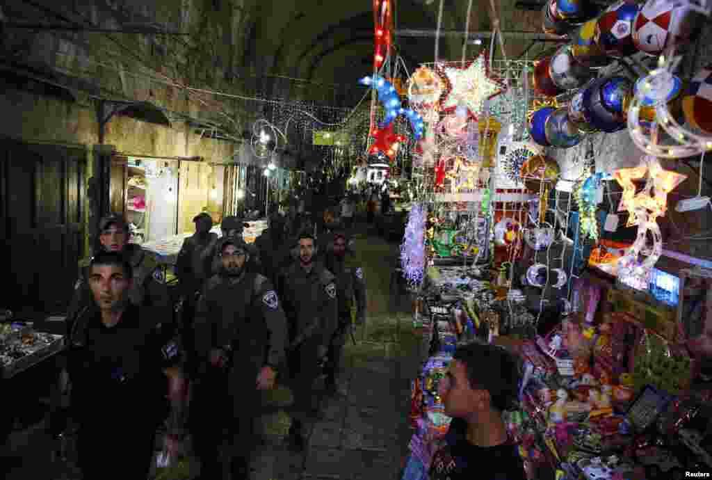 Lực lượng an ninh Israel đi tuần ngang qua một cửa hàng bán đồ trang trí cho tháng lễ Ramadan trong khu phố cổ của Jerusalem, 8 tháng 7, 2013.