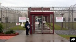 FILE - An employee of Immigration and Customs Enforcement's Stewart Detention Center in Lumpkin, Ga., waiting at the front gate of the facility, April 13, 2009.