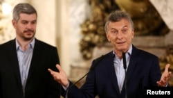 FILE - Argentina's President Mauricio Macri speaks next to Cabinet Chief Marcos Pena during a news conference at the Casa Rosada Presidential Palace in Buenos Aires, Oct. 23, 2017.