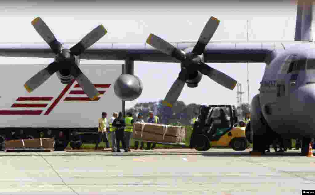 A worker uses a forklift to load coffins containing some of the remains of the victims of the crashed Malaysia Airlines MH17 plane on to a Dutch military aircraft before its departure to the Netherlands at Kharkiv airport, Ukraine, July 24, 2014.