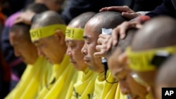 Relatives of victims of a South Korean ferry sinking that killed more than 300 a year ago, have their heads shaved during a rally against the government's plans in Seoul, South Korea, April 2, 2015.