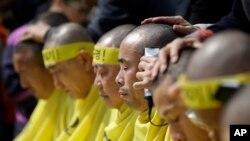 Keluarga korban kapal feri Korea Selatan yang tenggelam setahun yang lalu mencukur rambut di kepala mereka hingga gundul, memprotes rencana pemberian kompensasi pemerintah di Seoul, 2 April 2015 (AP Photo/Lee Jin-man)