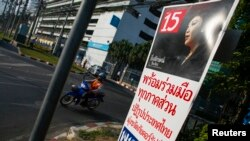 FILE - A motorcyclist rides past an election campaign poster of the ruling Pheu Thai Party, featuring a portrait of Prime Minister Yingluck Shinawatra, in central Bangkok, Jan. 3, 2014.