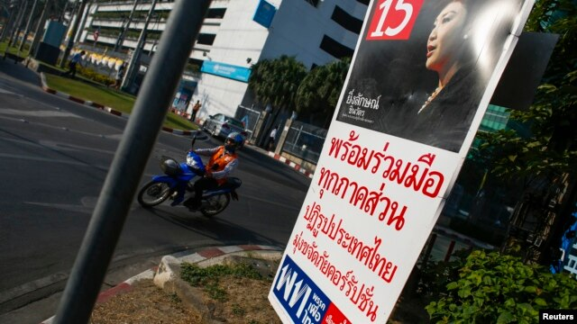 A motorcyclist rides past an election campaign poster of the ruling Pheu Thai Party, featuring a portrait of Prime Minister Yingluck Shinawatra, in central Bangkok on January 3, 2014.