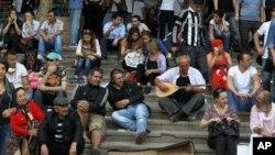 Para demonstran meneruskan aksi protes dengan duduk di tangga taman Gezi di Lapangan Taksim, Istanbul, Turki (15/6).