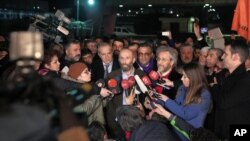 Can Dundar, the editor-in-chief of opposition newspaper Cumhuriyet, center right, and Erdem Gul, the paper's Ankara representative, center left, speak to the media outside Silivri prison near Istanbul, after their release, Feb. 26, 2016.
