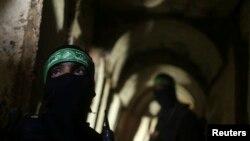Dua pejuang Palestina dari Brigade Izz el-Deen al-Qassam tampak siaga di dalam terowongan di Jalur Gaza (18/8).