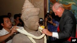 Walter Timoshuk, right, president of Norton Simon Museum of Art in Pasadena, California, places flowers onto a 10th century Cambodian sandstone statue returned from the United States during a handover ceremony at the Council of Ministers in Phnom Penh, Ju