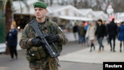 "A French soldier patrols the Christmas market along Champs Elysees in Paris as part of the ""Vigipirate"" security plan, Dec. 23, 2014."