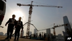Para pekerja tengah berjalan keluar dari sebuah konstruksi bangunan di Pusat Distrik Bisnis di Beijing, China (20/1).