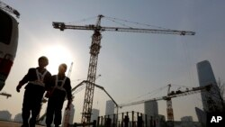 工人们离开北京的一处建筑工地。(2015年1月20日资料照)