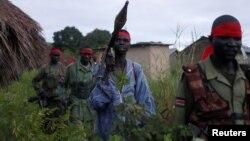 FILE - Sudan People's Liberation Army (SPLA-IO) rebels walk during an assault on government Sudan People's Liberation Army (SPLA) soldiers in the town of Kaya, South Sudan, Aug. 26, 2017.