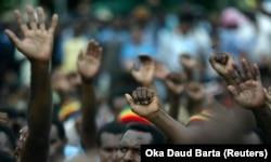Para pengunjuk rasa Papua mengangkat tangan mereka saat rapat umum menyerukan kemerdekaan di Jayapura, Papua,16 Oktober 2008. (Foto: Reuters/Oka Daud Barta)