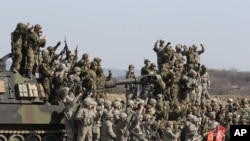 South Korean and U.S. army, gray, soldiers cheer after a live fire drill during the annual Foal Eagle maneuvers near Rodriguez Range in Pocheon, south of the demilitarized zone that divides the two Koreas, South Korea, March 15, 2012.