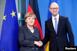 German Chancellor Angela Merkel, left, and Ukraine's Prime Minister Arseniy Yatsenyuk appear after talks at the chancellery in Berlin, April 1, 2015.