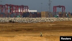 "FILE - An engineer walks through a part of a construction site of Chinese investment ""Colombo Port City"" in Colombo, February 20, 2015."
