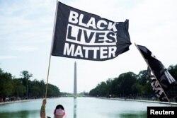 Muškarac drži zastava Black Lives Matters u Washingtonu.