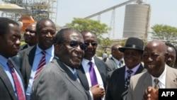 Le président Robert Mugabe du Zimbabwe, au centre, salue des chefs locaux à la mine Zimplats, près de Harare, le 13 Octobre 2011.